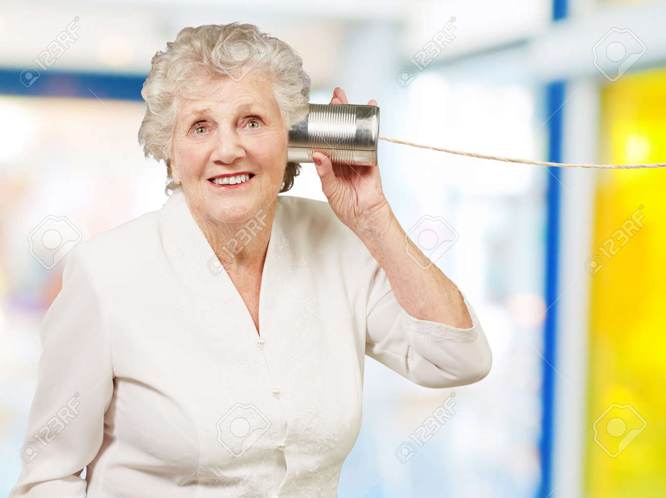 portrait of senior woman hearing with metal tin can indoor Stock Photo - 14252079