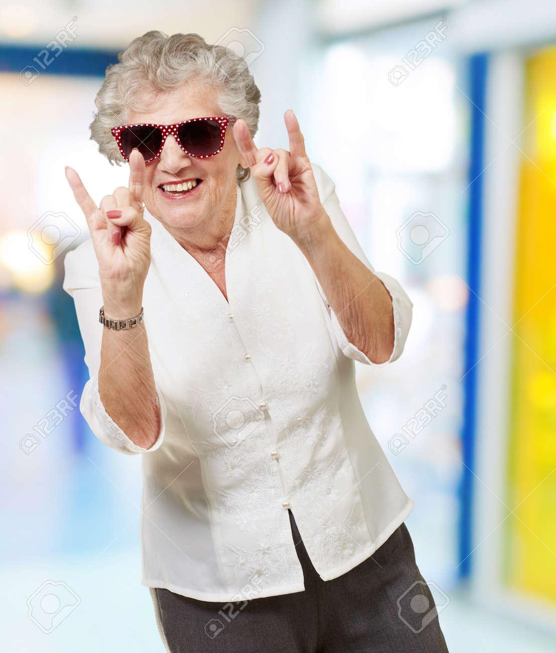 portrait of a happy senior woman doing rock symbol indoor Stock Photo - 14252134
