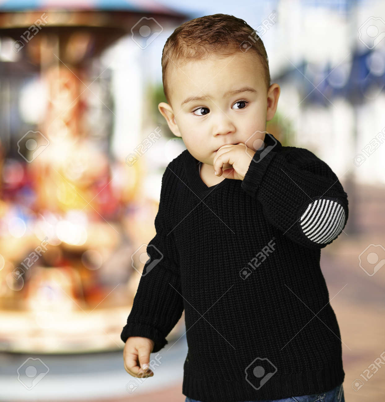 worried little boy against a carousel background Stock Photo - 14438794