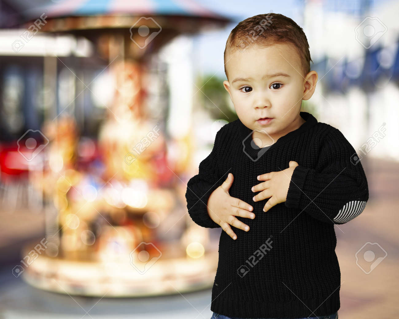 adorable boy touching his stomach against a carousel background Stock Photo - 14438812