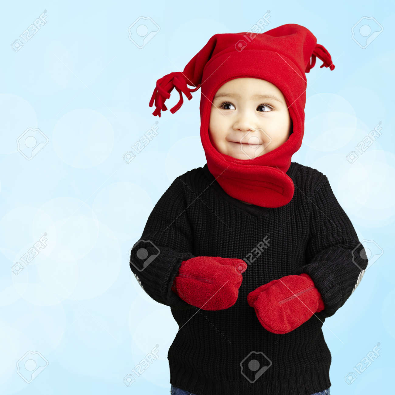 happy boy wearing winter clothes against a blue background Stock Photo - 14438793
