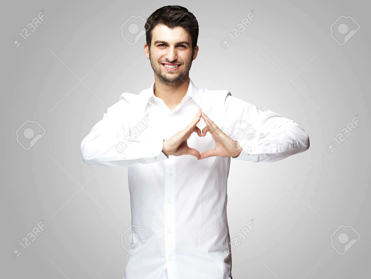 portrait of young man doing heart gesture against a grey background Stock Photo - 14438847
