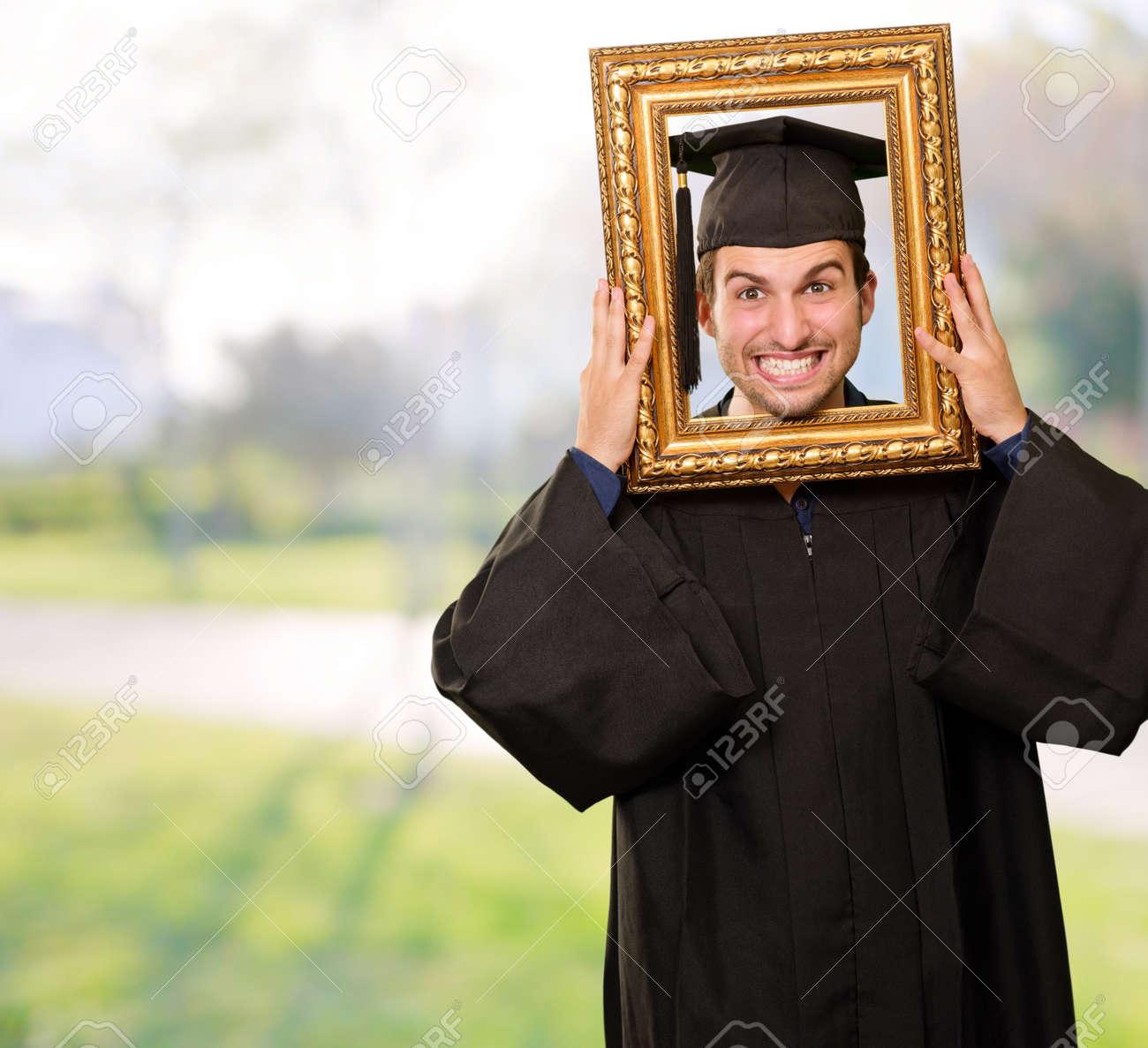 Graduate man looking through a frame, outdoor Stock Photo - 14683282