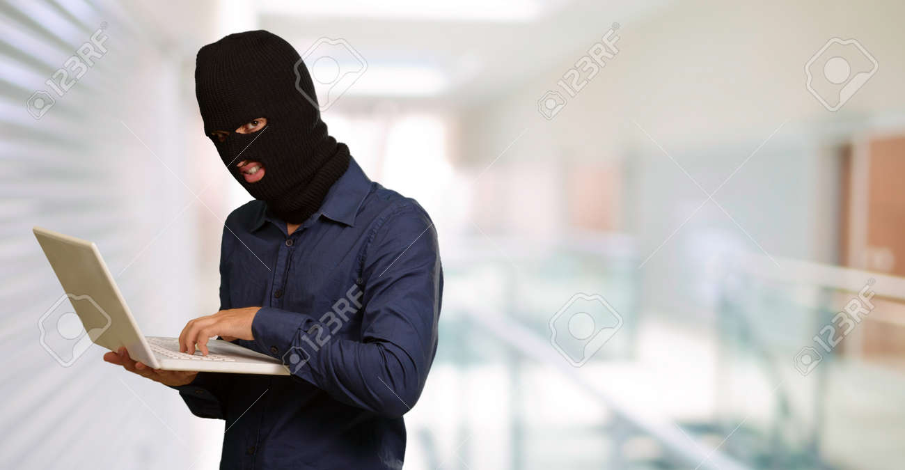 young male thief holding laptop, indoor Stock Photo - 14704164