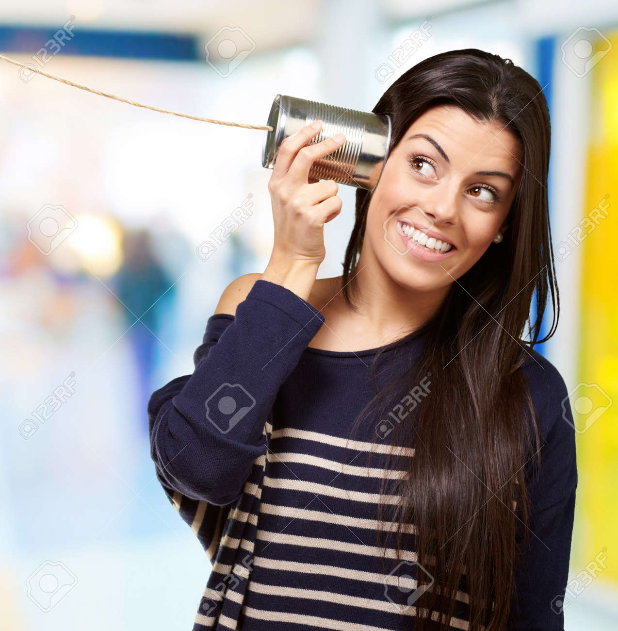 Young woman hearing using a metal tin can at crowded place Stock Photo - 14704163
