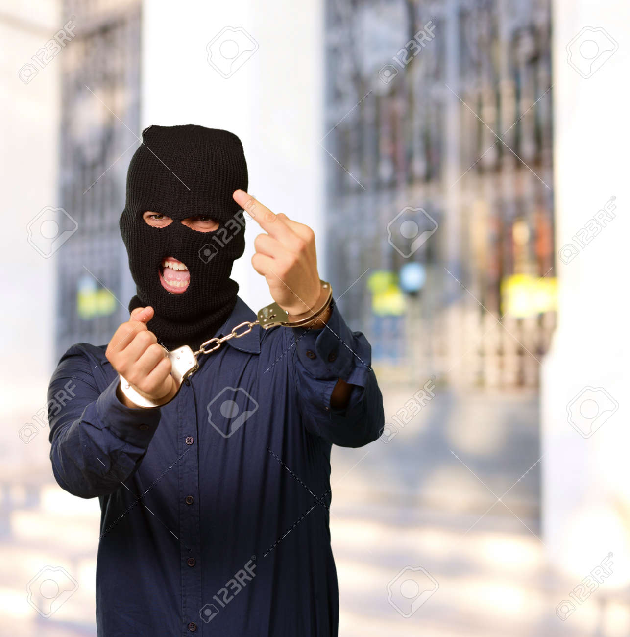 angry criminal man locked in handcuffs, outdoor Stock Photo - 14760881