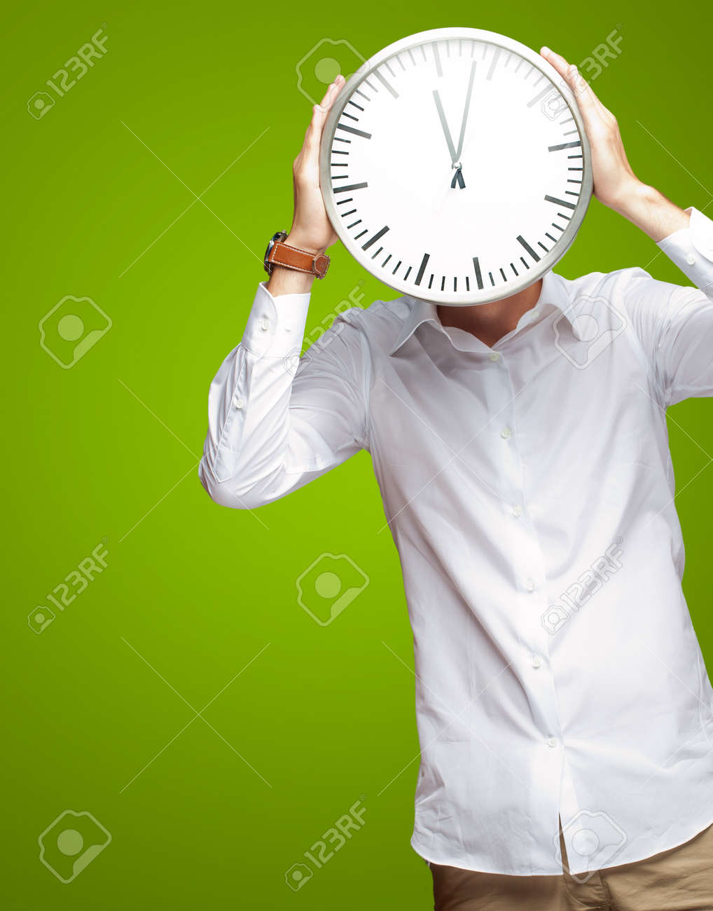 Young Man Holding Big Clock Covering His Face On Green Background Stock Photo - 15186874