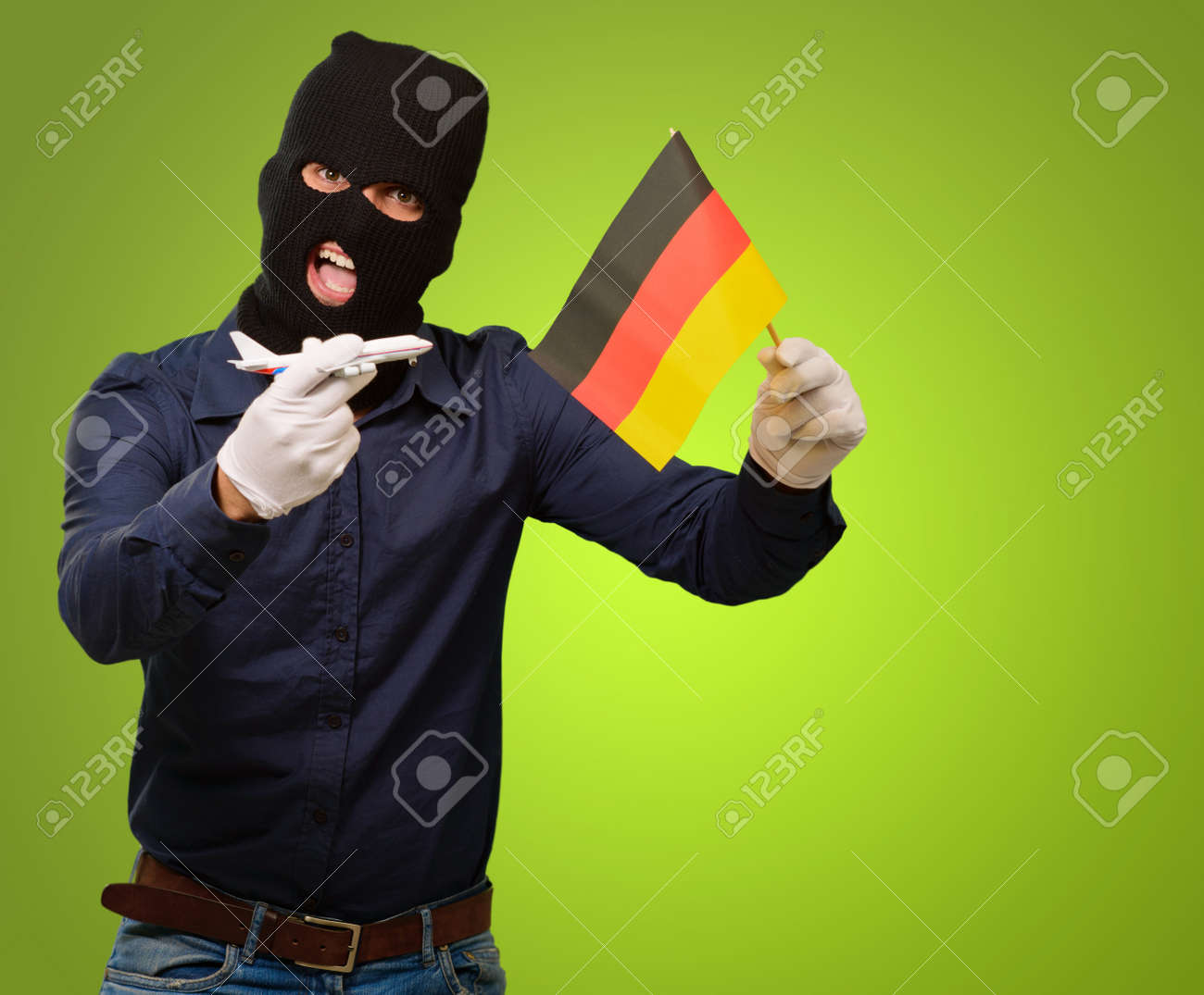 Man wearing a robber mask and holding airplane miniature and flag on green background Stock Photo - 15187204