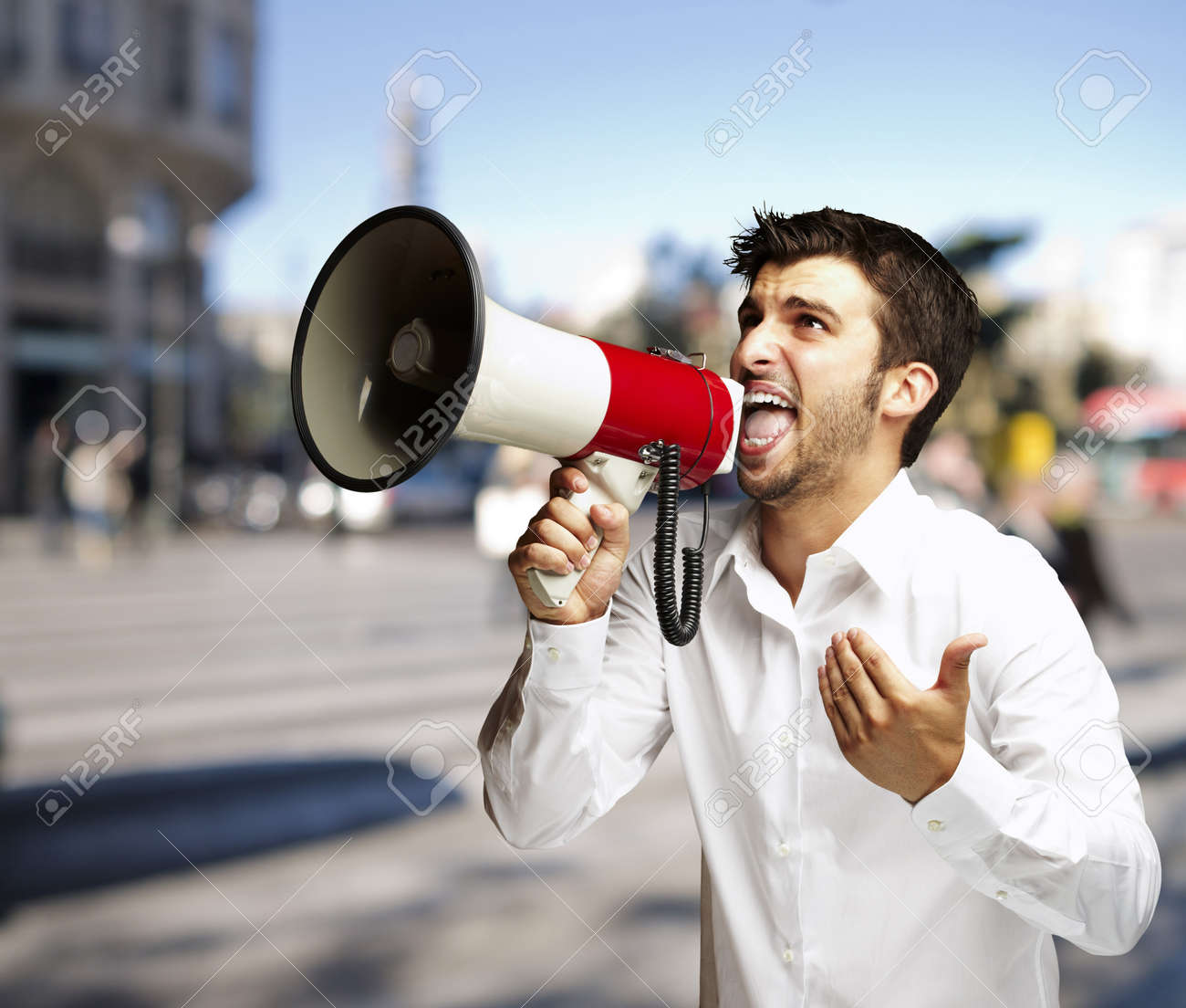 portrait of young man shouting with megaphone at street Stock Photo - 15104582
