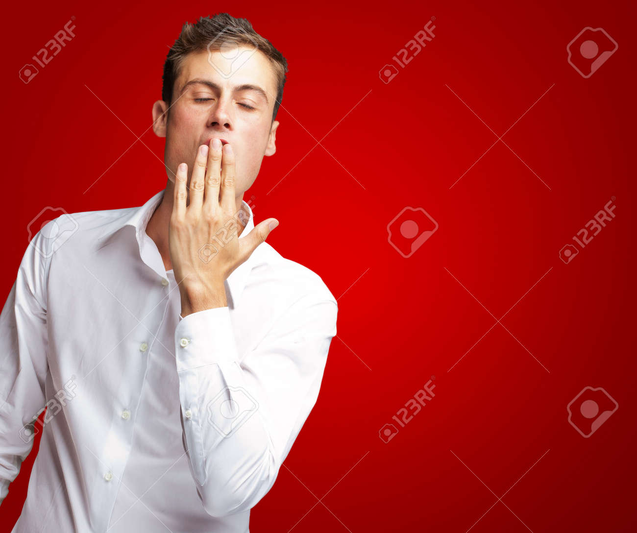 Portrait Of Young Man Yawning Isolated On Red Background Stock Photo - 15850731