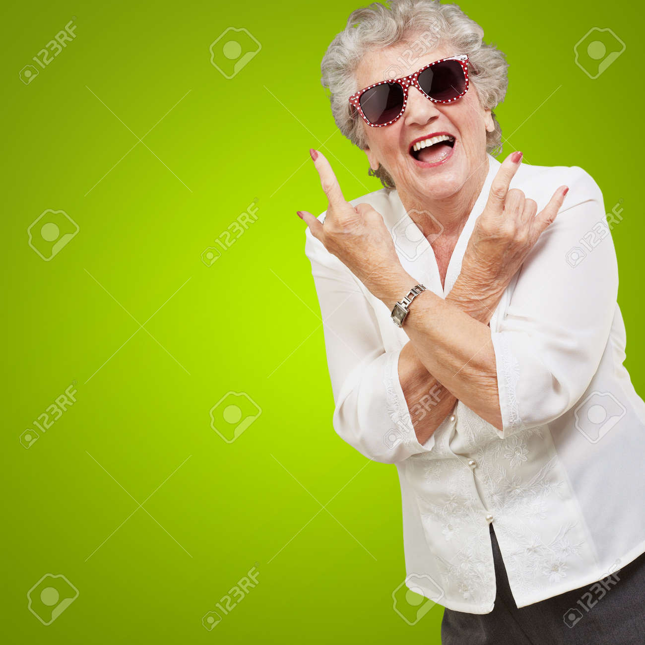 Senior woman wearing sunglasses doing funky action isolated on green background Stock Photo - 16039340