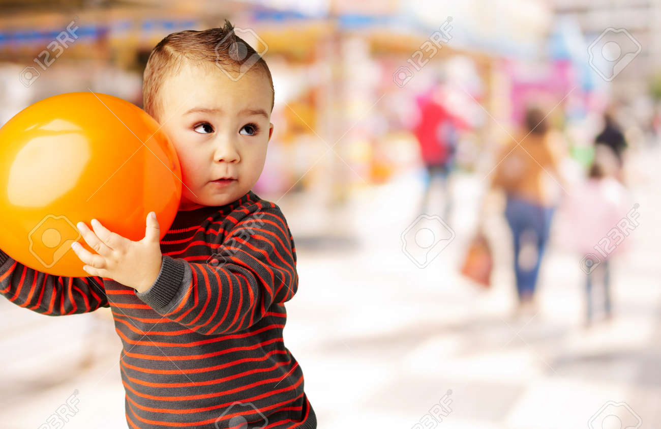 kid holding a orange balloon at mall Stock Photo - 16140032