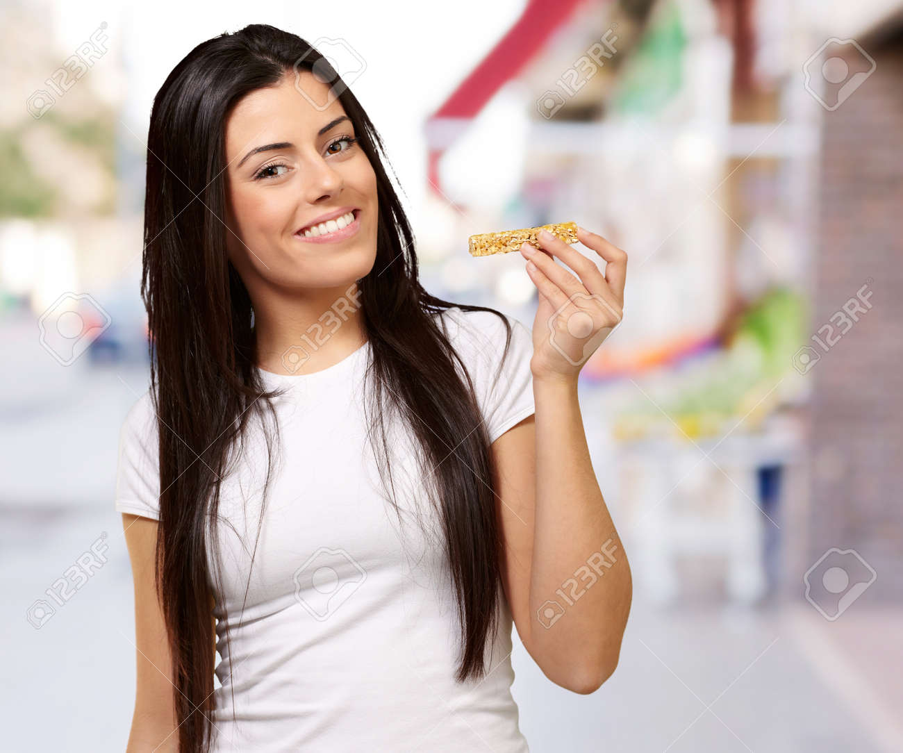 portrait of young woman eating cereal bar at street - 16140150