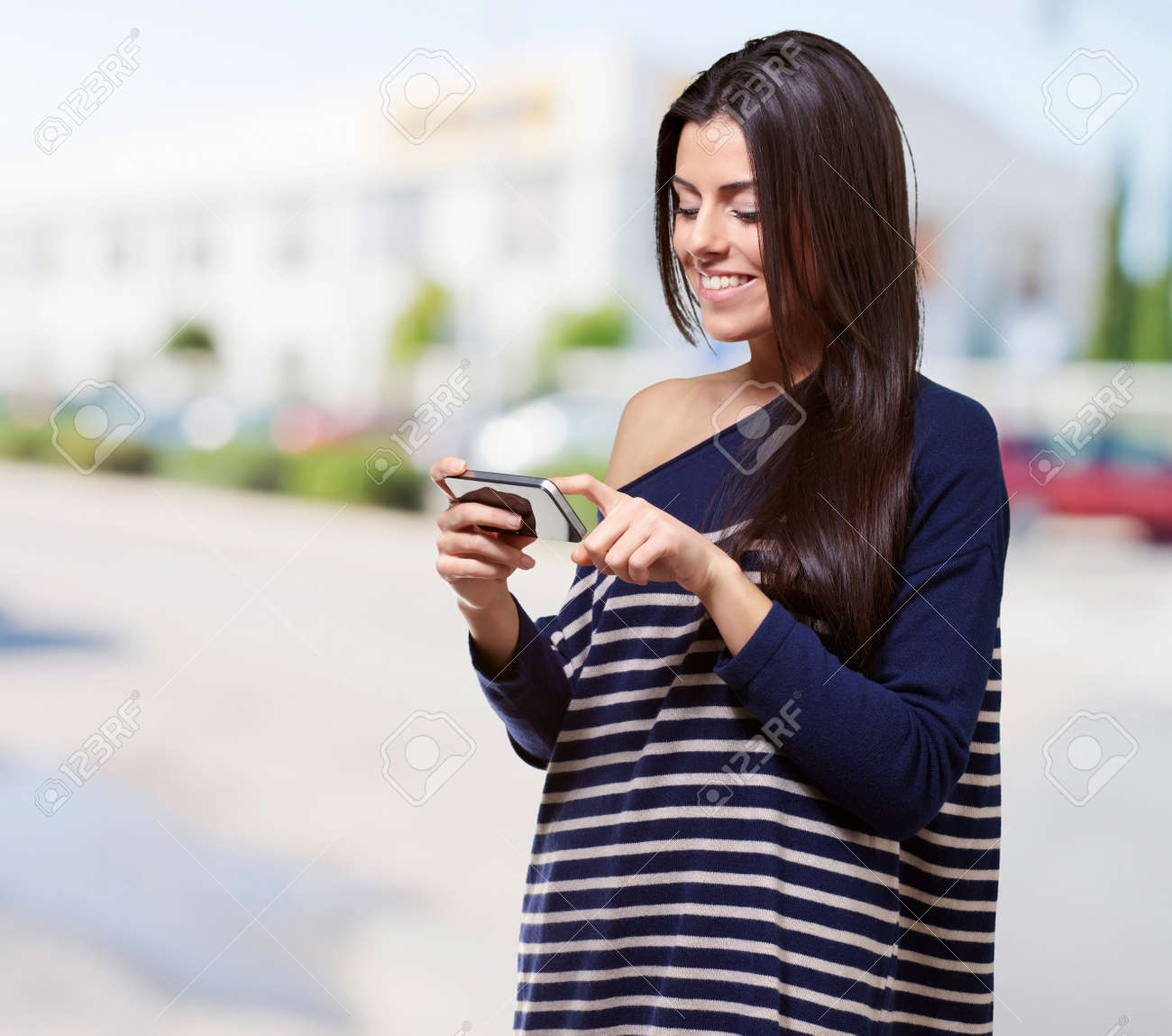 portrait of young woman touching a modern mobile at street - 16252258