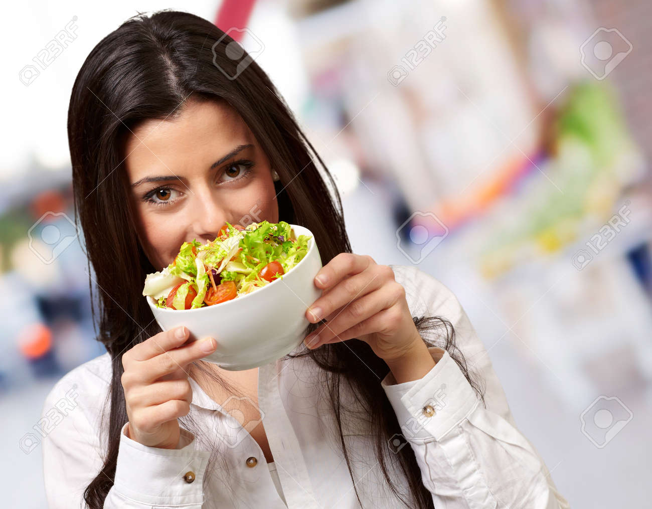 portrait of young woman holding a fresh salad at street - 16252295