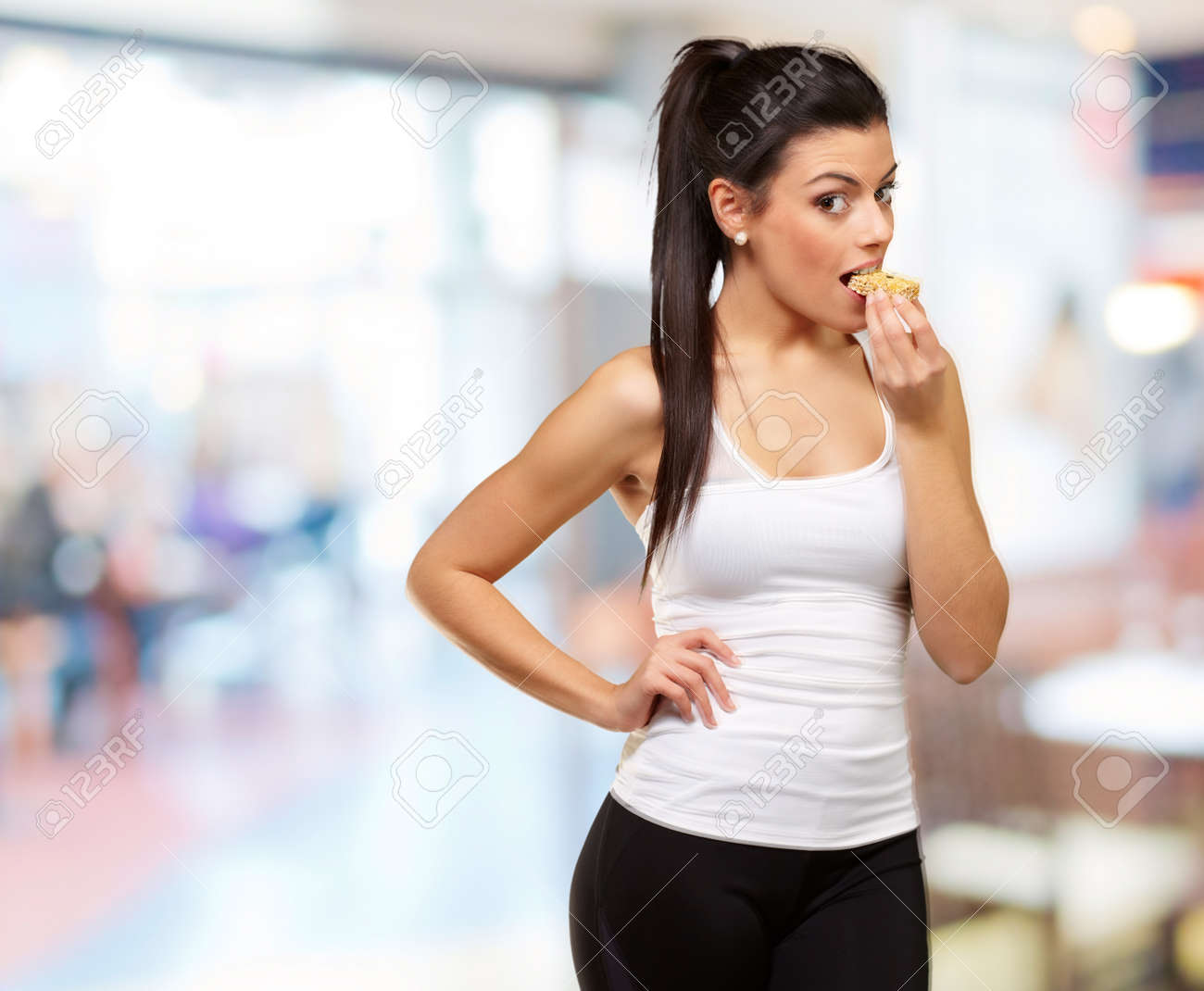 young healthy girl eating a cereal bar indoor - 16252332