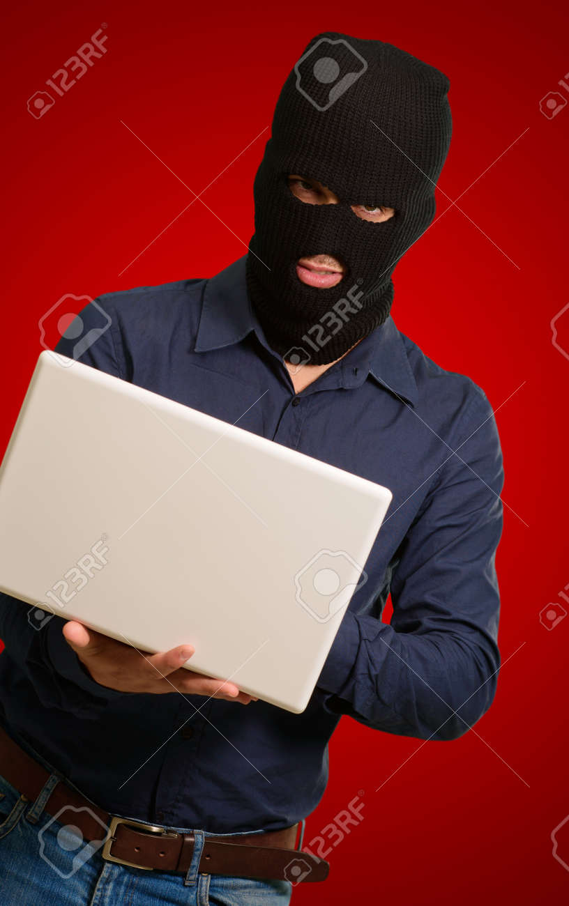 young male thief holding laptop isolated on red background Stock Photo - 16290539