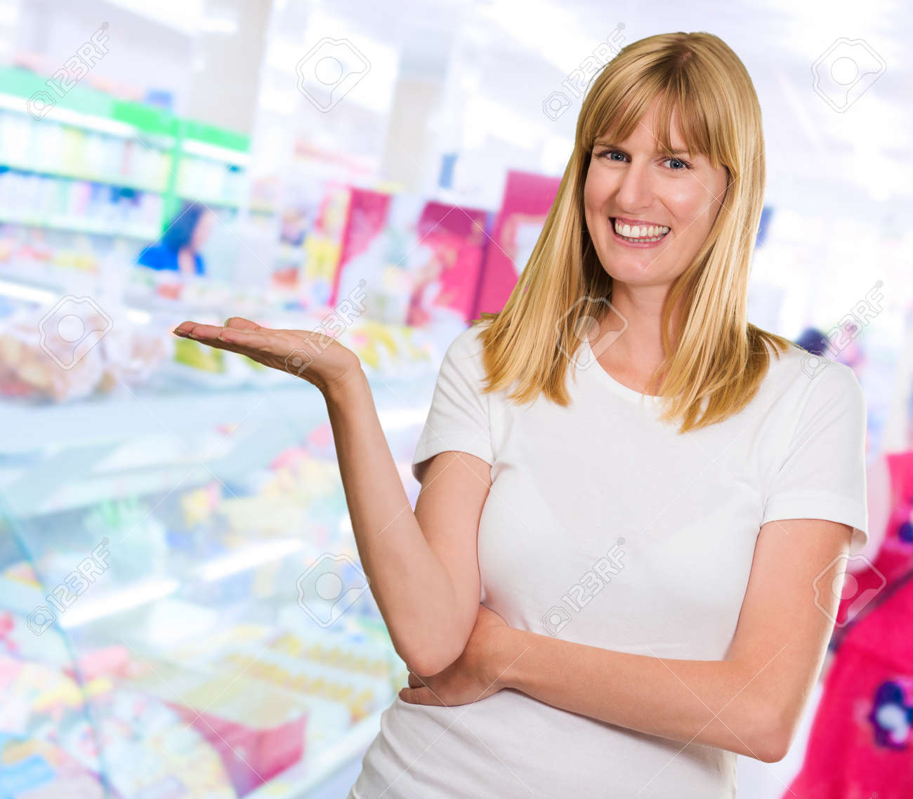 Happy Woman Presenting at a supermarket Stock Photo - 16291077