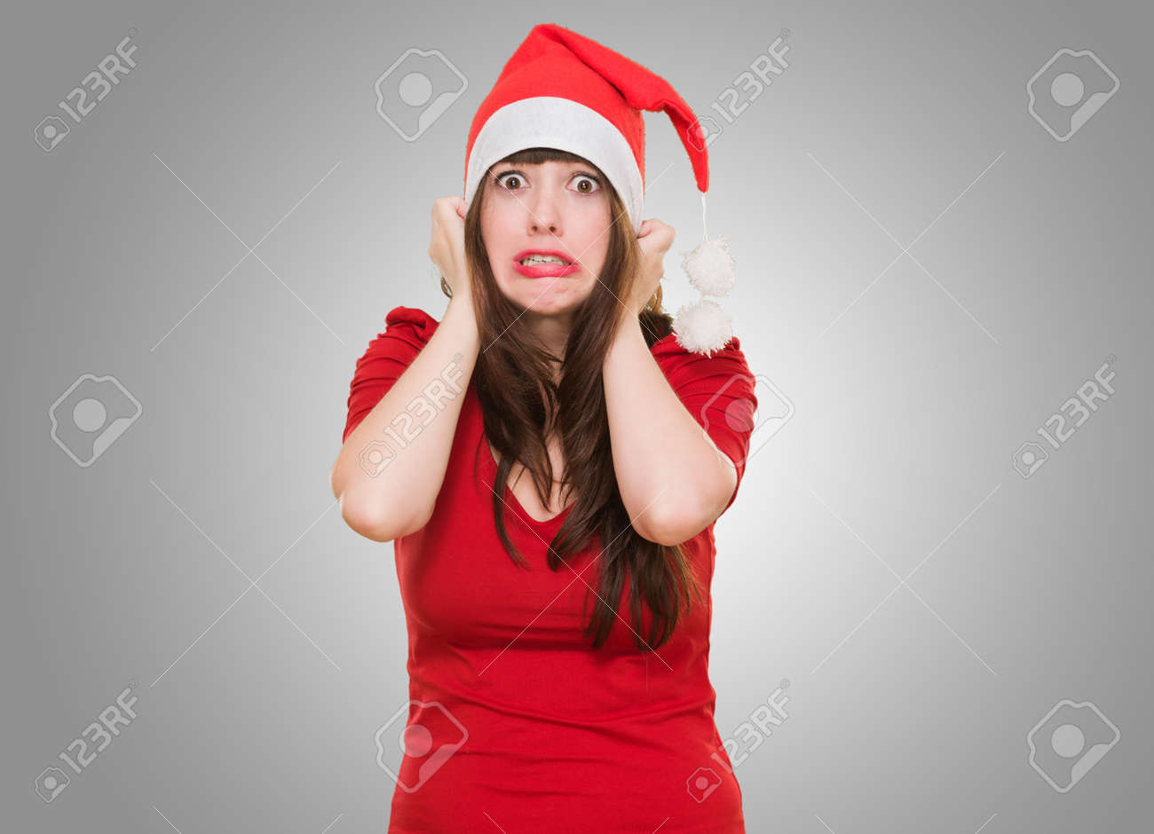 scared woman wearing a christmas hat against a grey background - 16290879