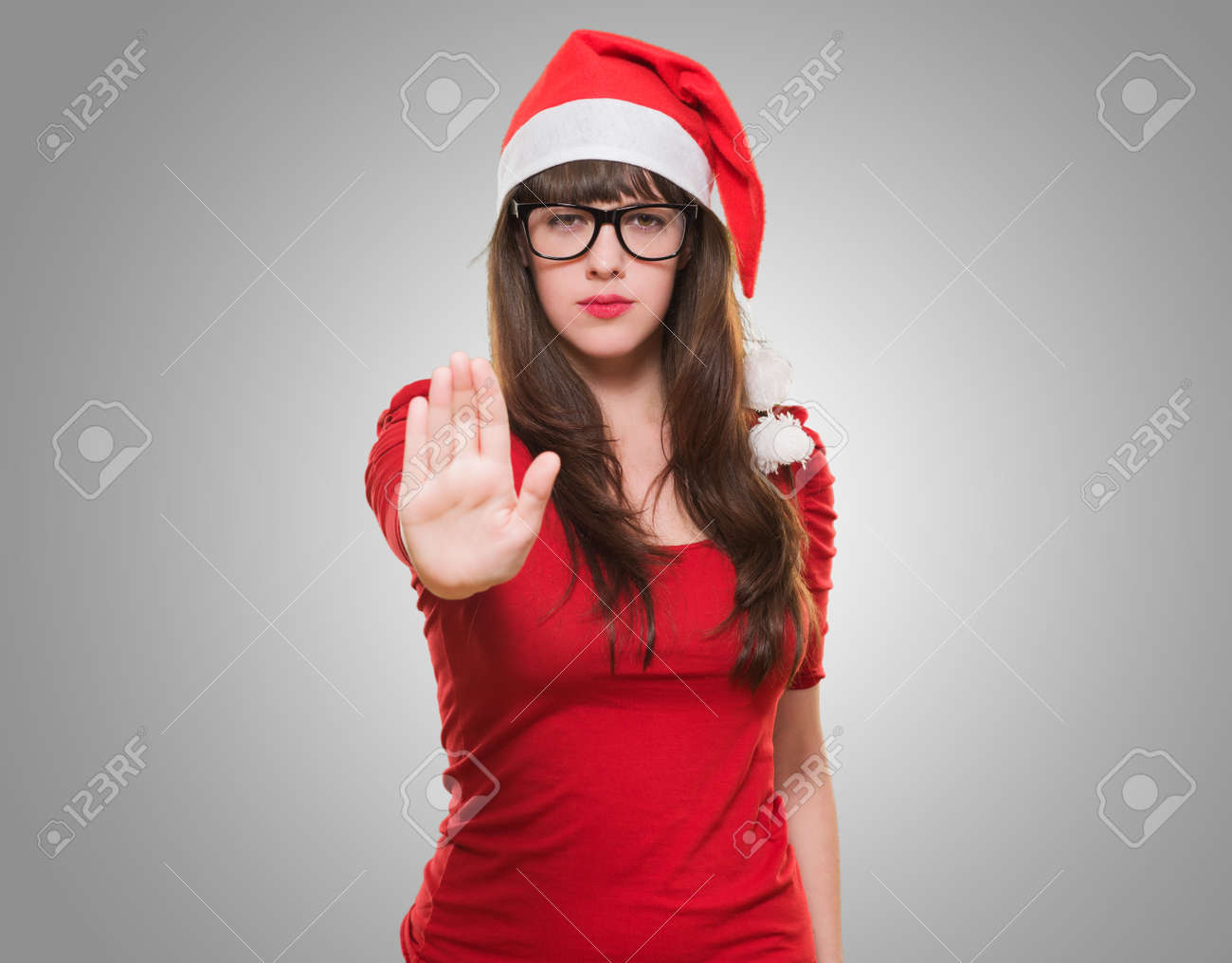 christmas woman doing a stop gesture against a grey background - 16290925