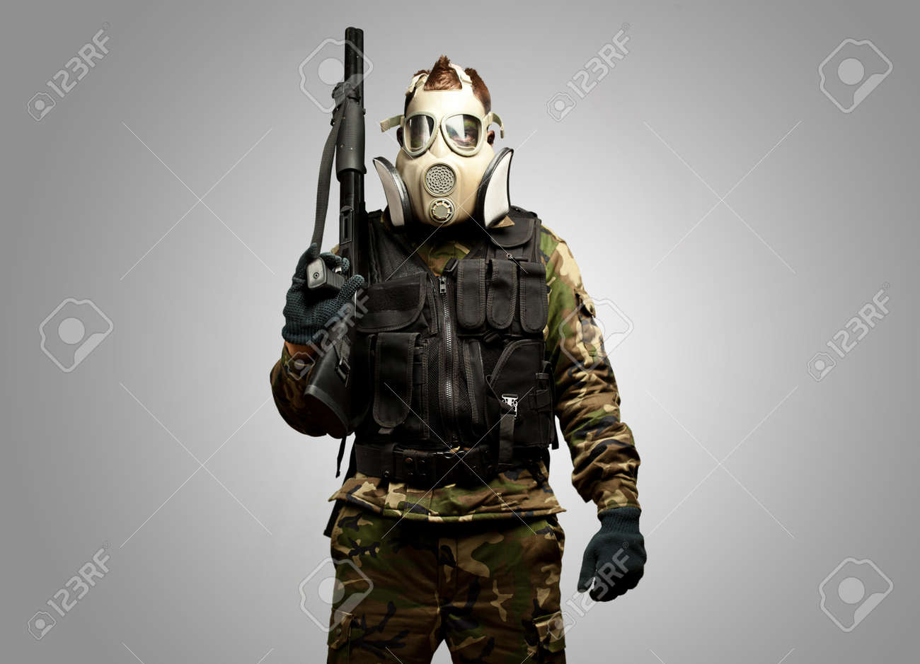 Portrait Of A Soldier With Gas Mask against a grey background - 16690538