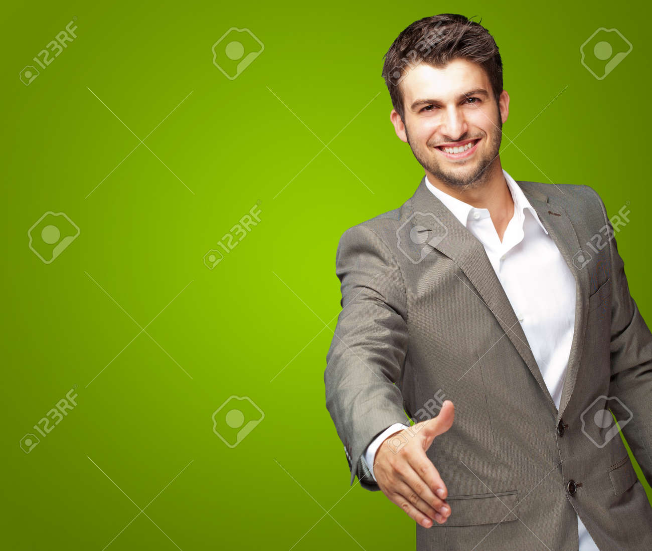 Portrait Of Young Businessman In A Suit Holds Out His Hand For A Handshake On Green Background - 16690492