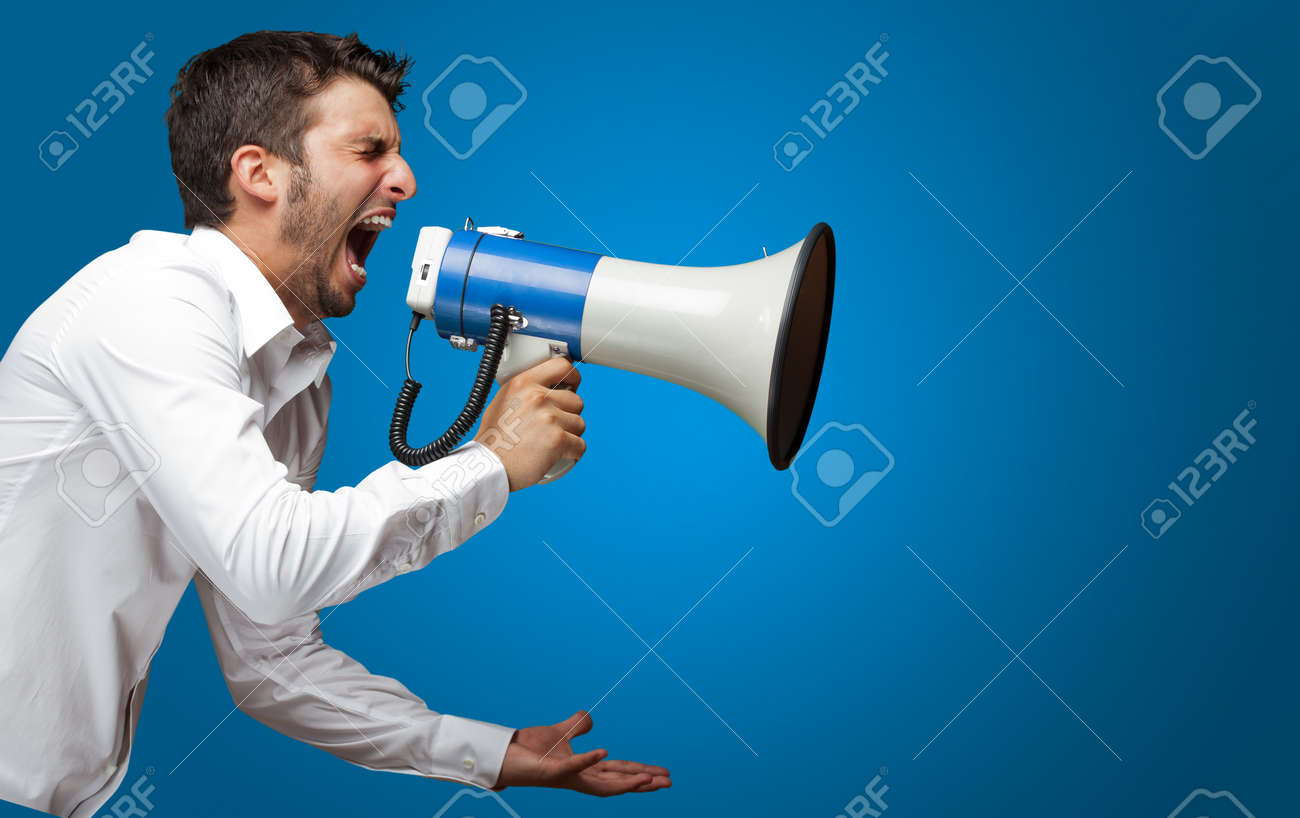 Portrait Of A Man Yelling Into A Megaphone Against Blue Background Stock Photo - 16690618