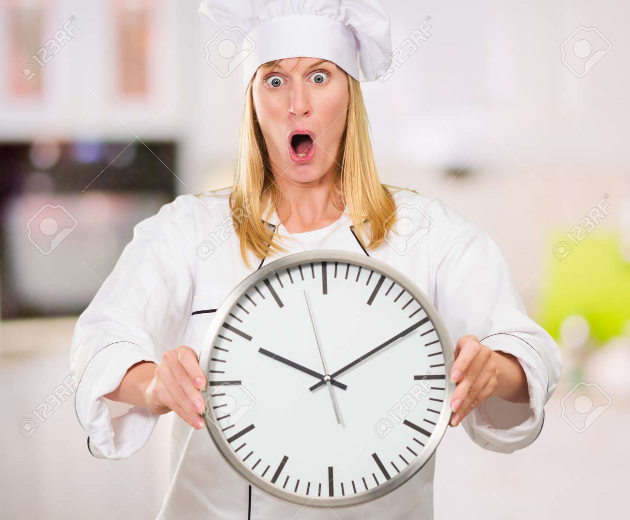 Stupendous Shocked Female Chef Holding Clock In A Kitchen Indoor Home Interior And Landscaping Transignezvosmurscom