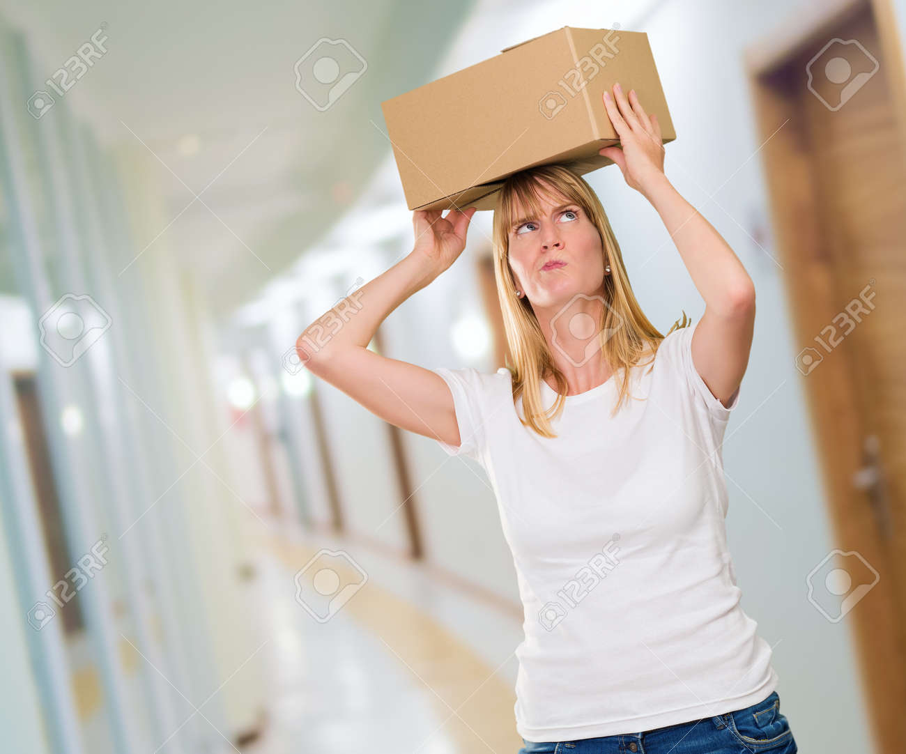 woman holding a box on her head in a passage way Stock Photo - 16672464