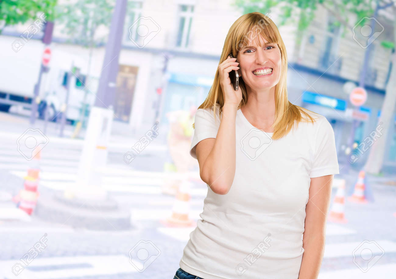 happy woman talking on a mobile at a street market, outdoor Stock Photo - 16672496