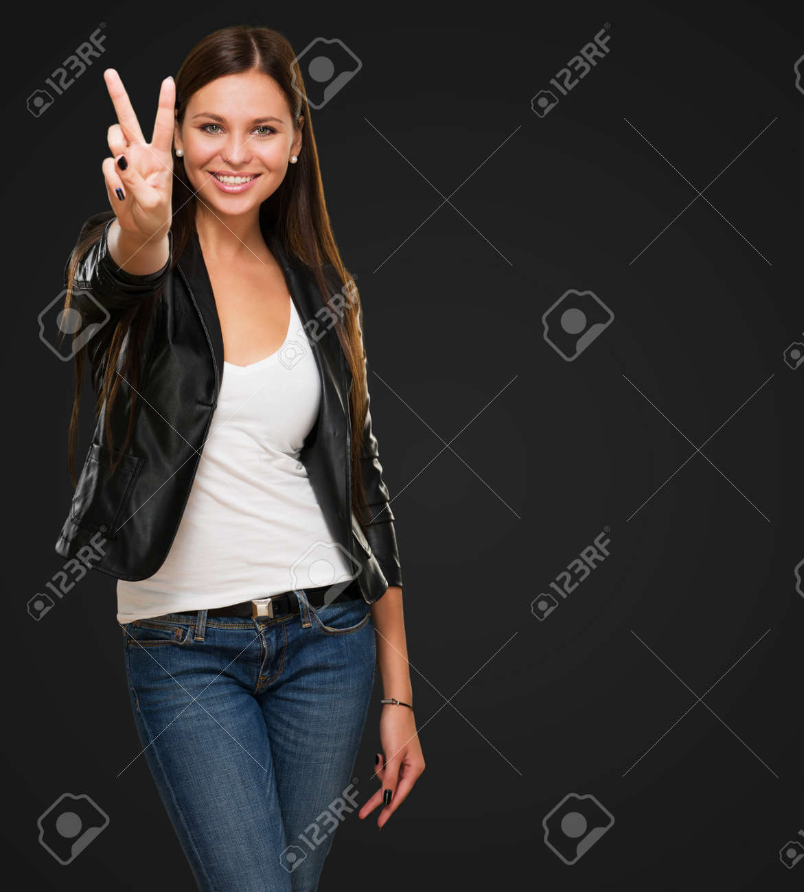 Beautiful Woman Giving Victory Sign against a black background - 16672549