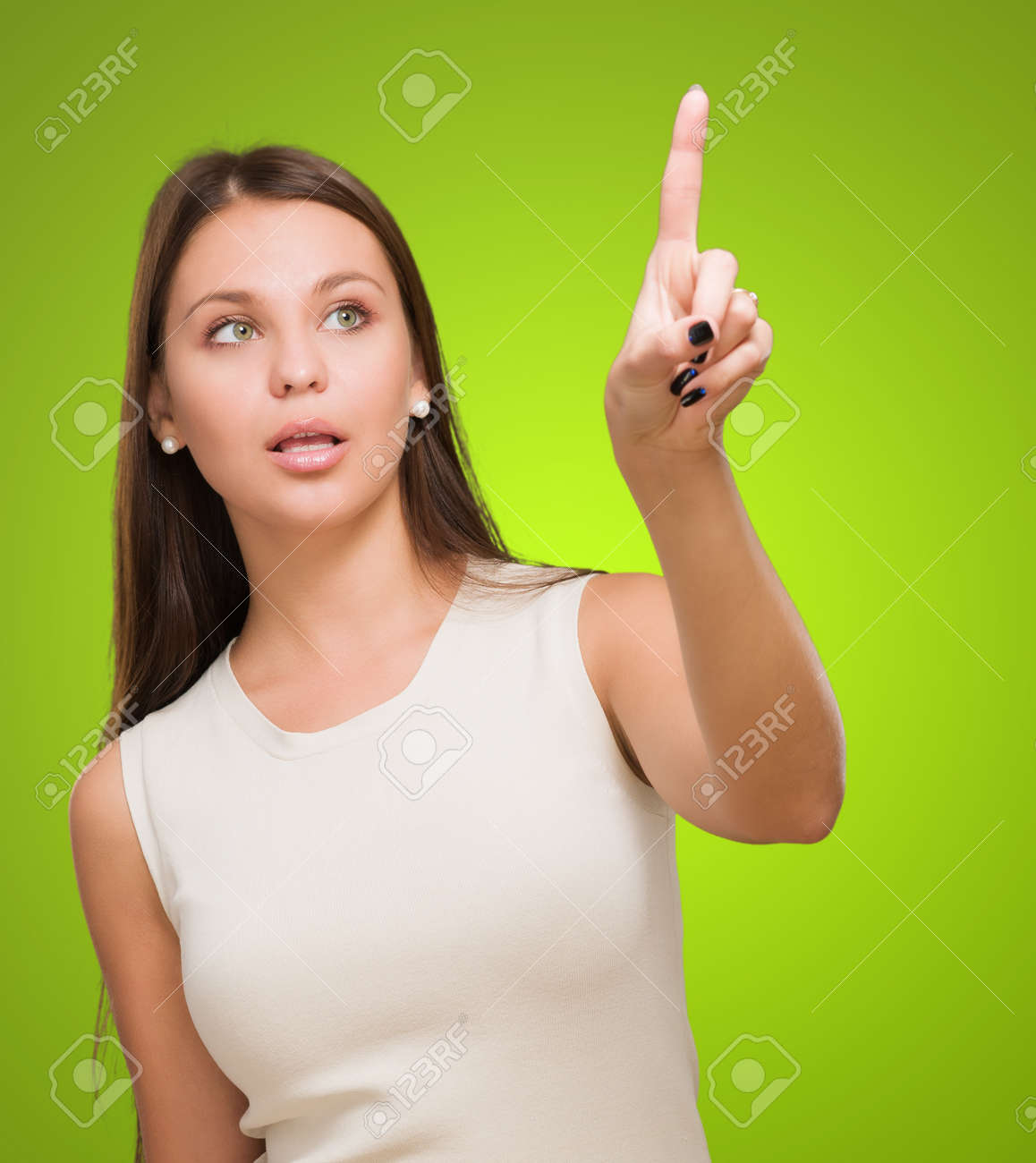 Portrait Of A Young Woman Pointing Up against a green background - 16671751