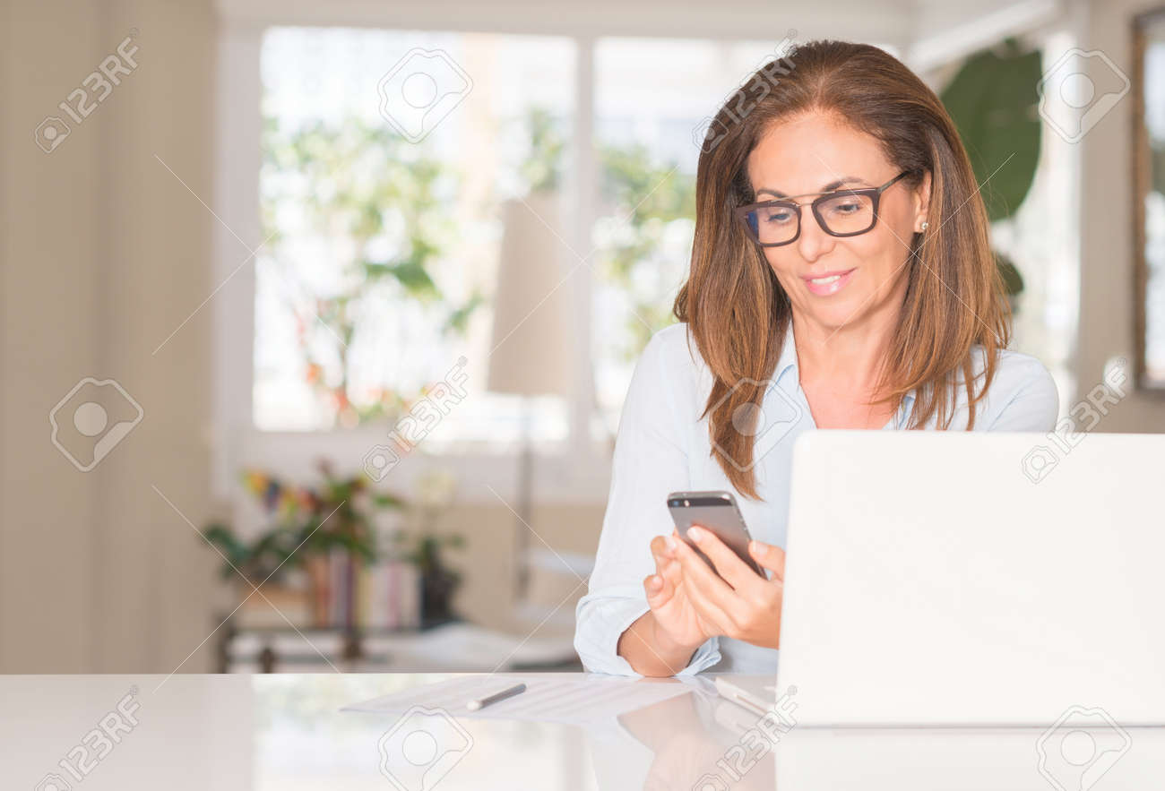 Middle age woman using smartphone and laptop, indoor - 104066520