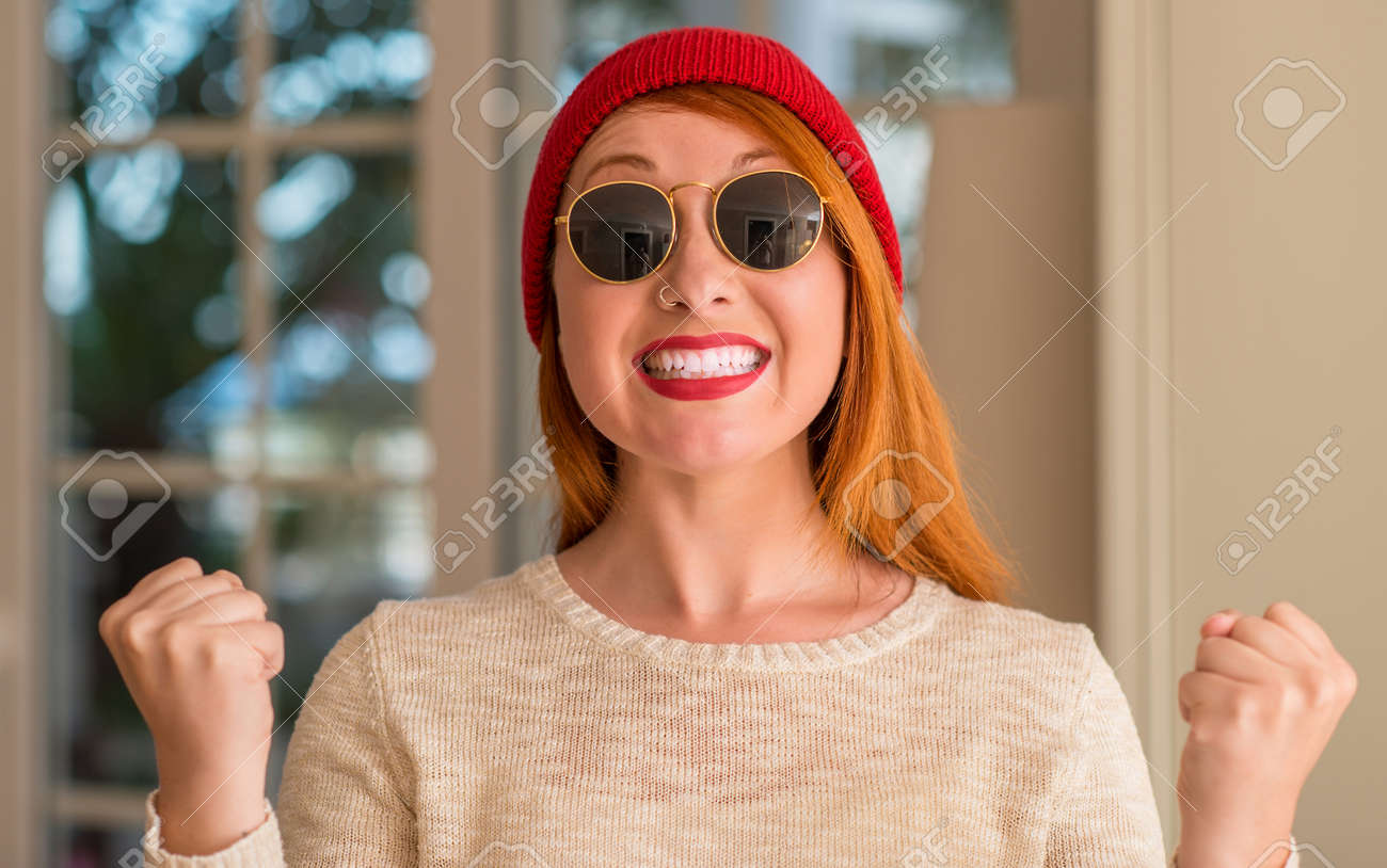 Stock Photo - Stylish redhead woman wearing wool cap and sunglasses  screaming proud and celebrating victory and success very excited c946c57fdb3
