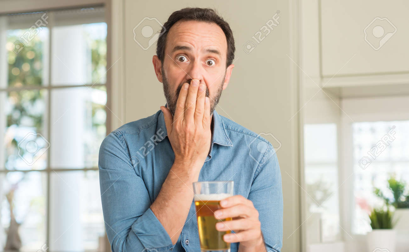 Middle age man drinking beer cover mouth with hand shocked with