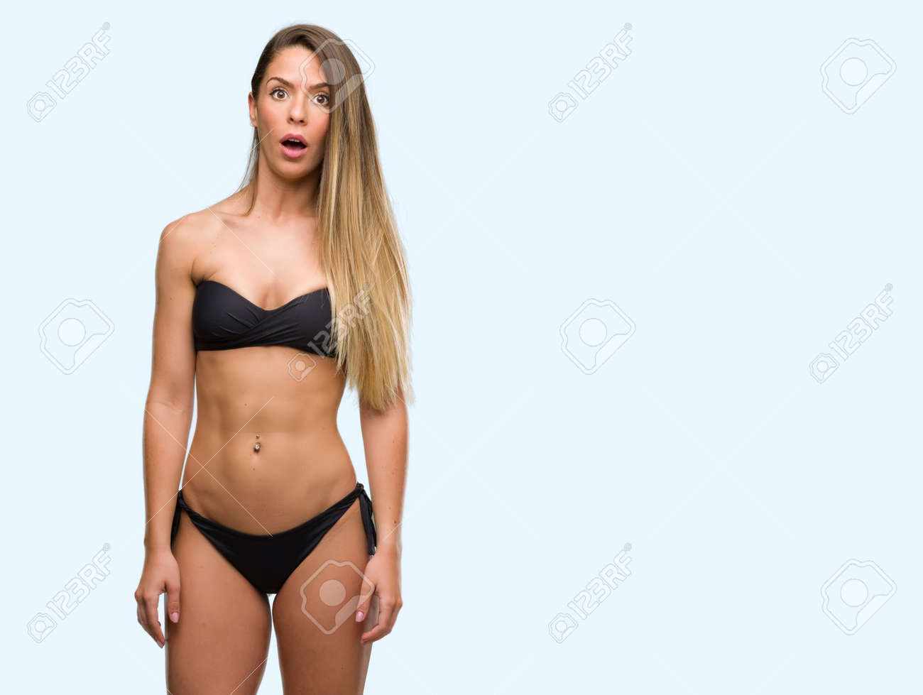 5d1df21041cec Beautiful young woman wearing black bikini scared in shock with a surprise  face