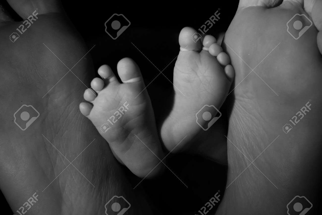 Parent dad feet with baby newborn feet between stock photo 5073114