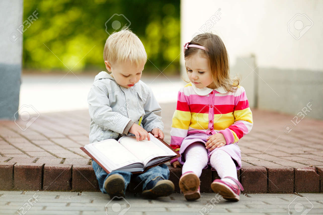 cute boy and girl reading a book Stock Photo - 16951772