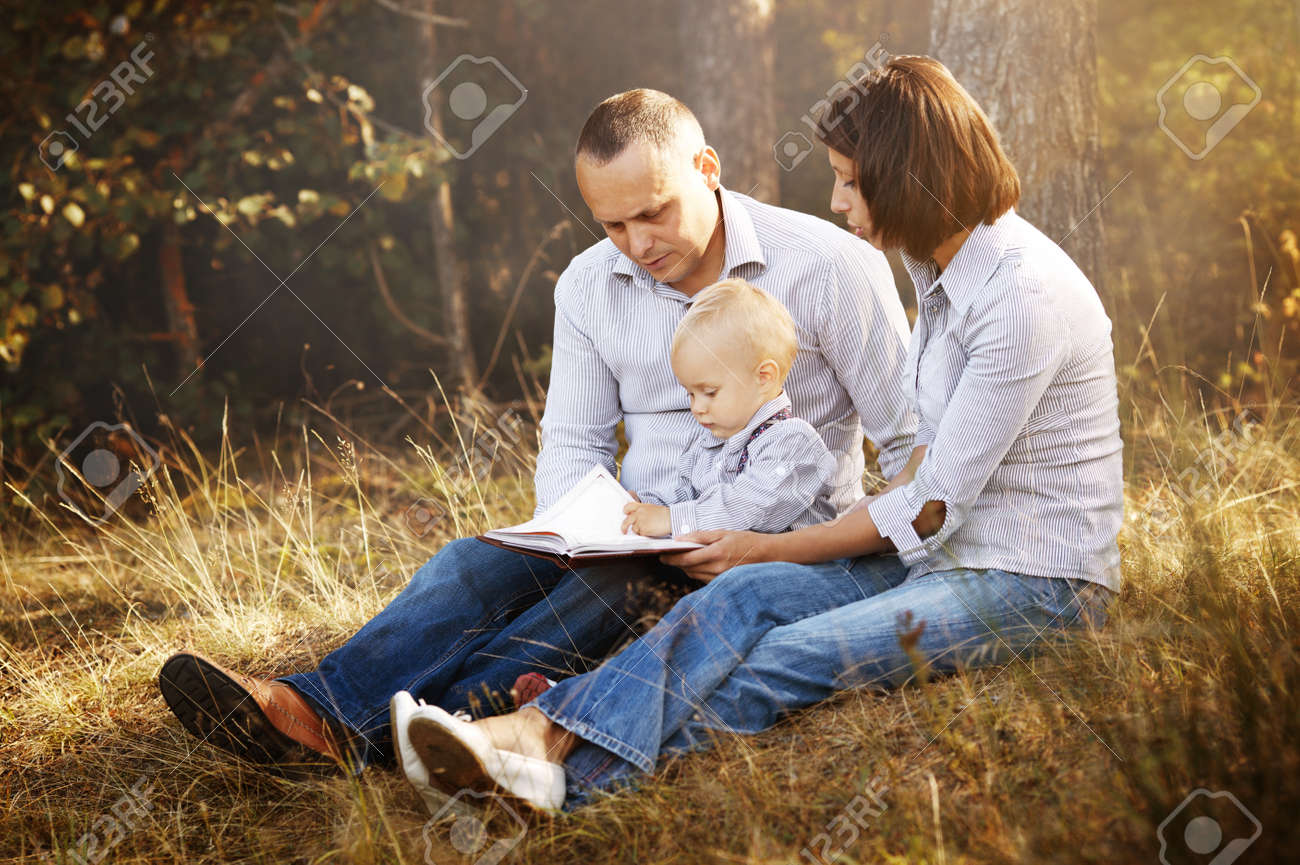 Happy family reading book in park Stock Photo - 23577146