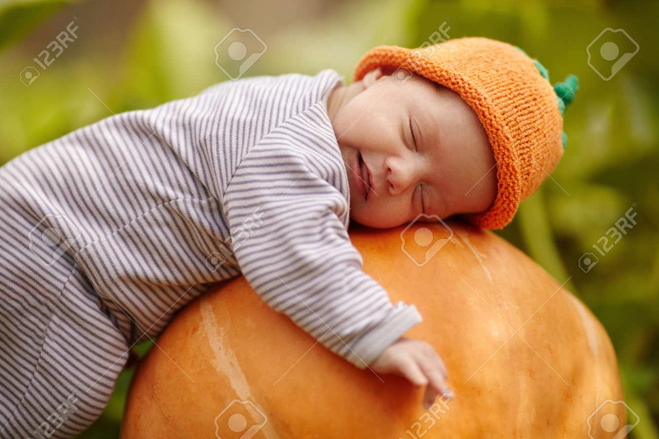 sweet baby with pumpkin hat sleeping on big orange pumpkin - 60656825