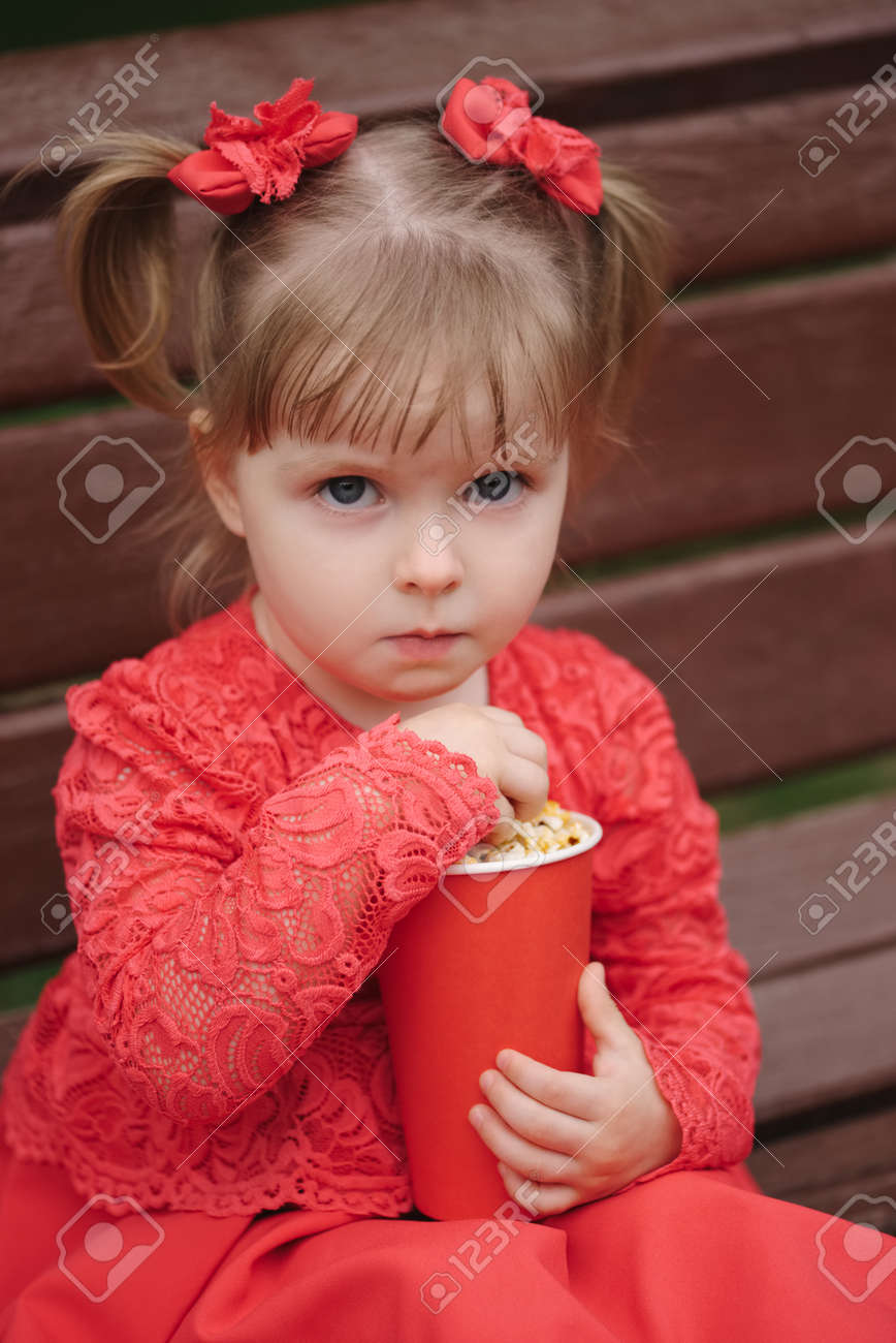 little girl with cup of popcorn in park stock photo picture and