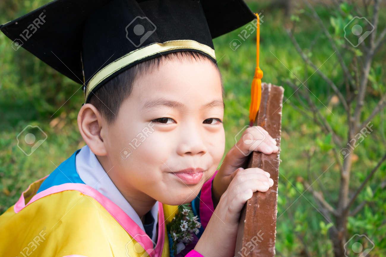 Chico Primaria Lleva Con Orgullo Su Gorra De Graduación Y Vestido