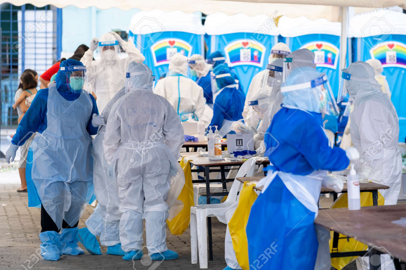 KUALA LUMPUR, MALAYSIA - MAY 15, 2020: Government health worker wearing a protective suit prepares to do the COVID-19 screening test to foreign migrant workers. Coronavirus disease 2019 outbreak. - 147239294