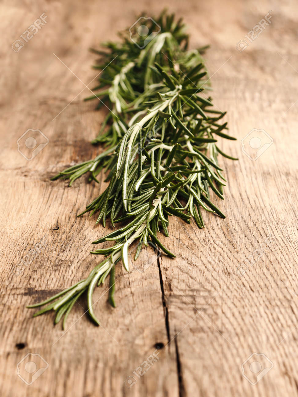 Twig of organic rosemary on a rustic wooden kitchen table, healthy food or ingredients concept - 145977013
