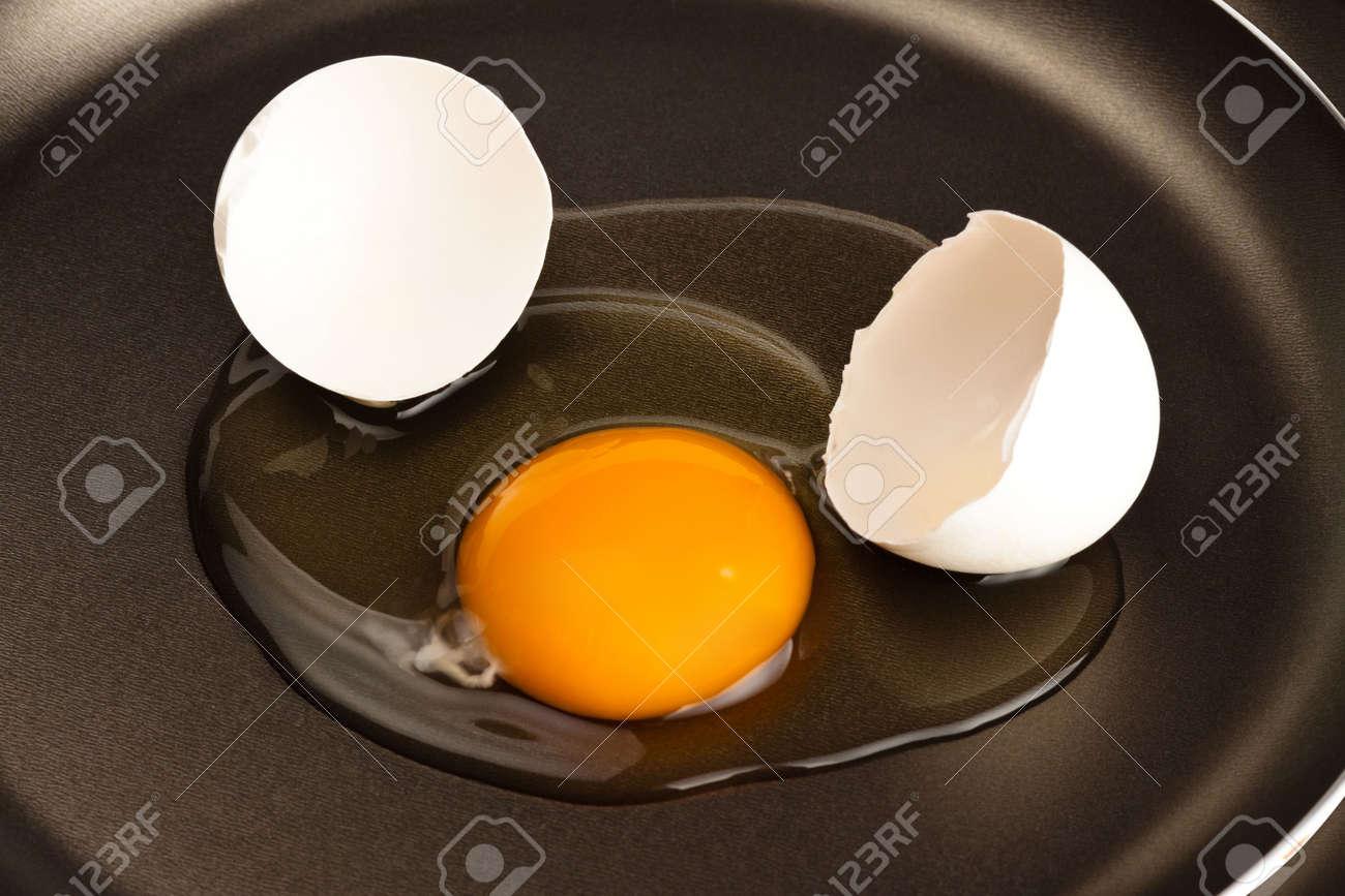 broken white egg on black pan Stock Photo - 5831269