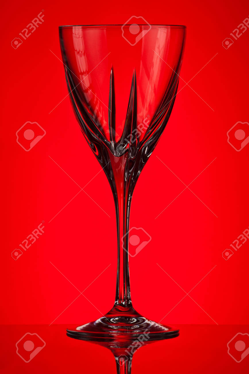 empty crystal glass on red background Stock Photo - 6822539