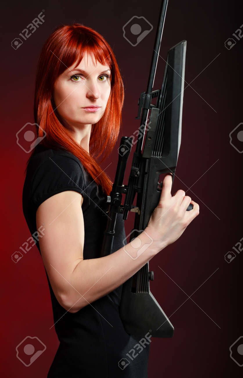 woman in black dress with sniper rifle, red background Stock Photo - 9246203