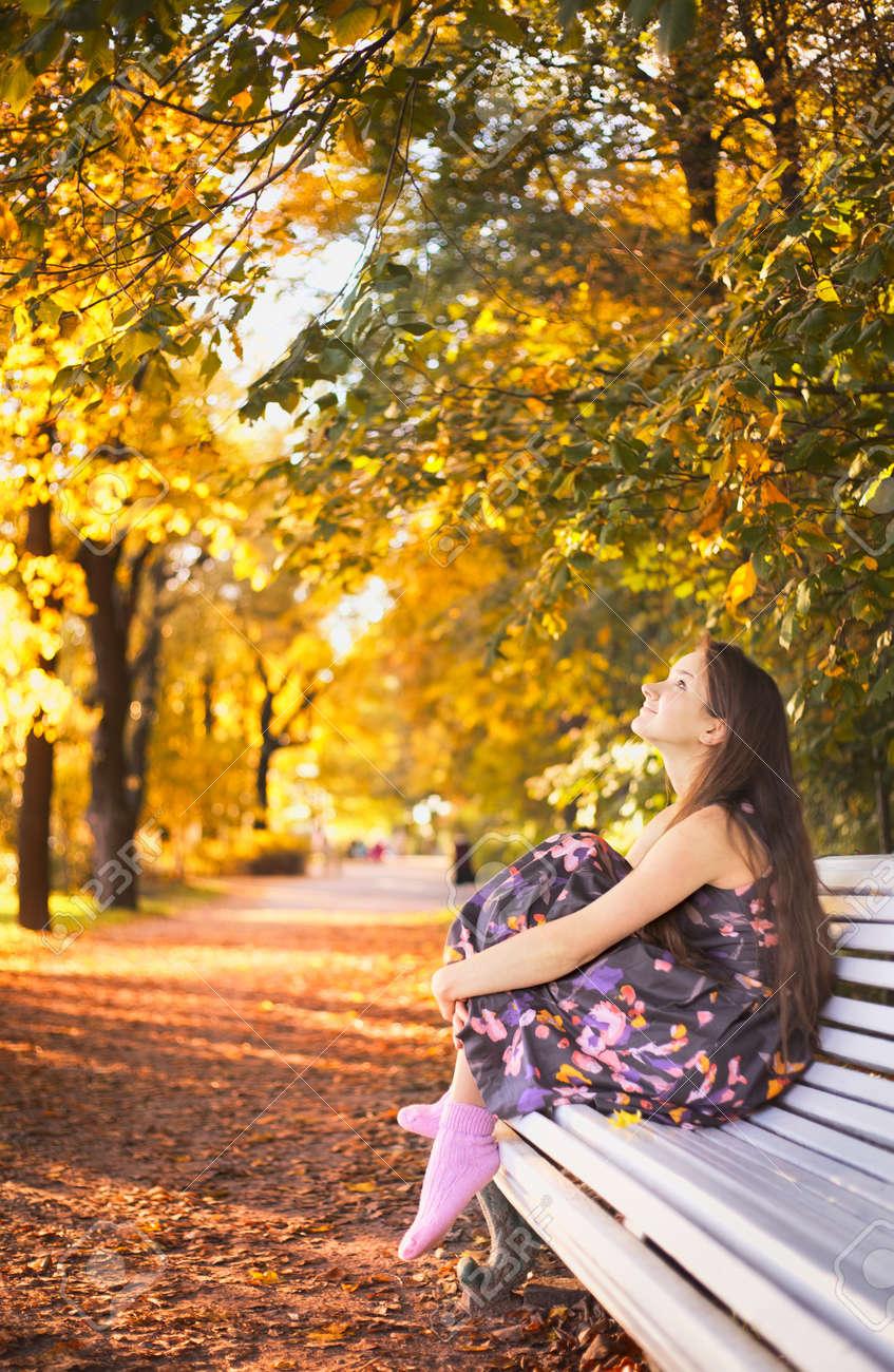 beautiful girl sitting on bench in autumn park Stock Photo - 11646785