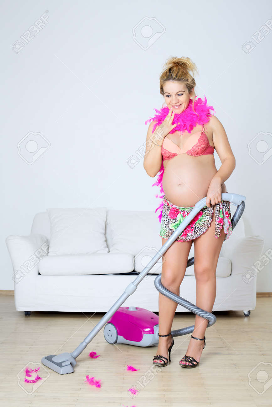 happy young pregnant woman with vacuum cleaner Stock Photo - 12477144