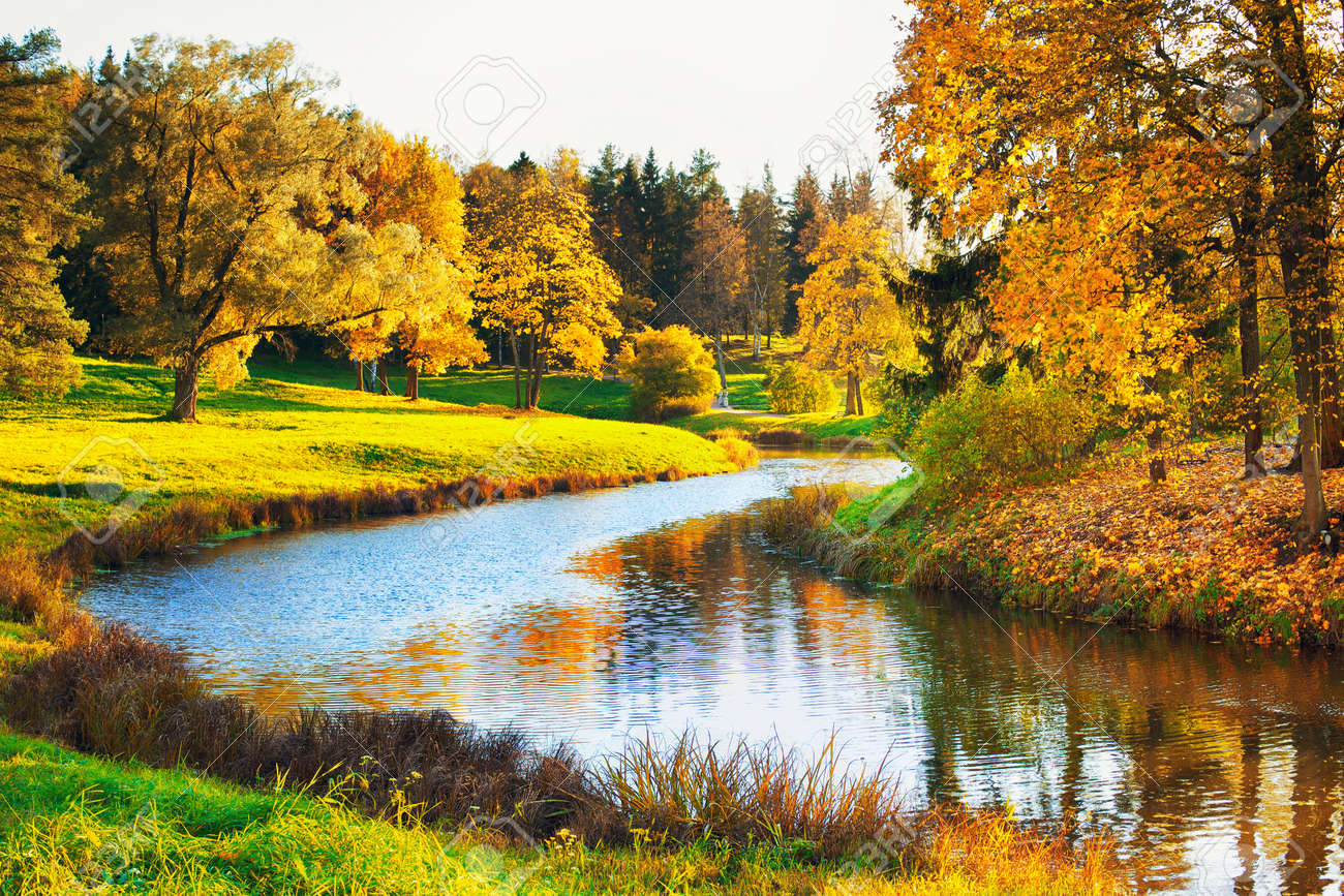 Autumn Landscape In Park With River And Blue Sky Stock Photo
